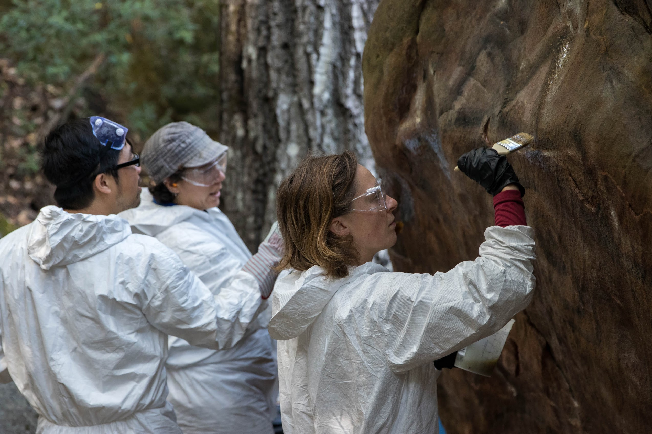 a woman in the foreground applies paint remover with a brush, while two participants discuss the removal process in the background