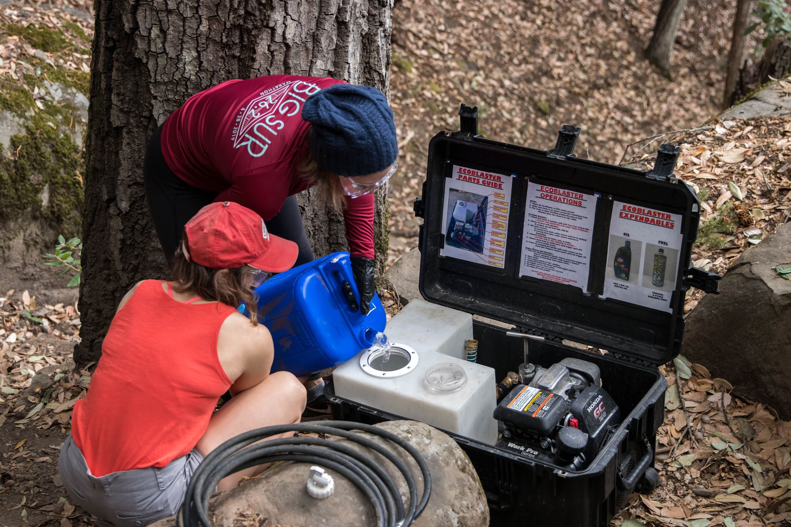 two volunteers ready the EcoBlaster pressure washer by adding water to its tank