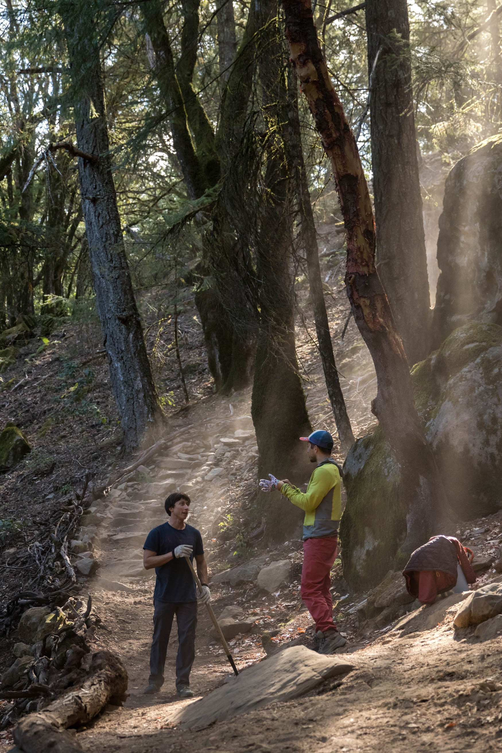 Two volunteers discussing trail restoration in a forest setting. The trail bends around a rock formation.