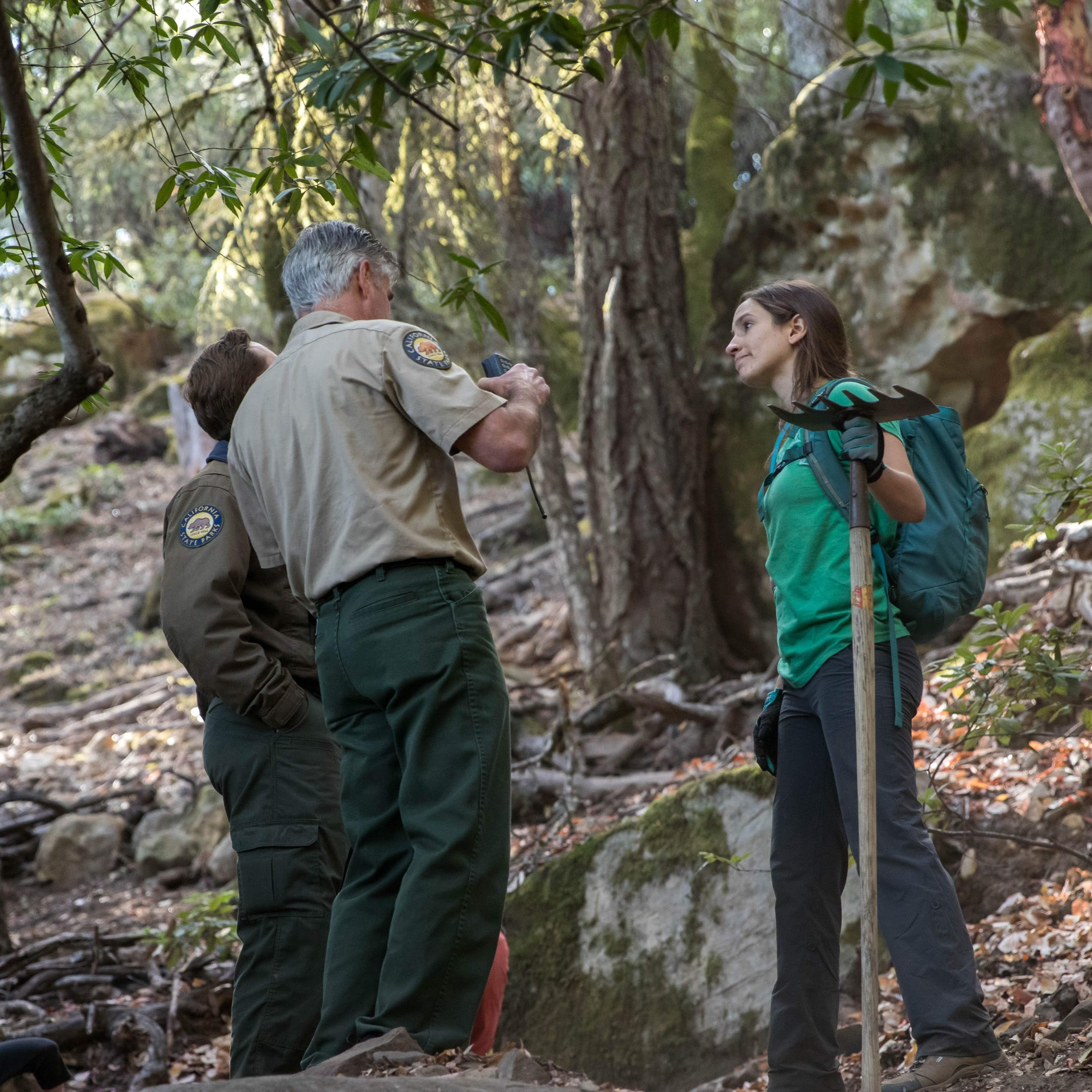 park representatives having a conversation with a BACC steward who is holding a trail restoration tool