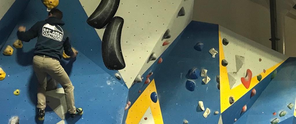 a climber wearing a Bay Area Climbers Coalition hoodie climbing an indoor boulder problem