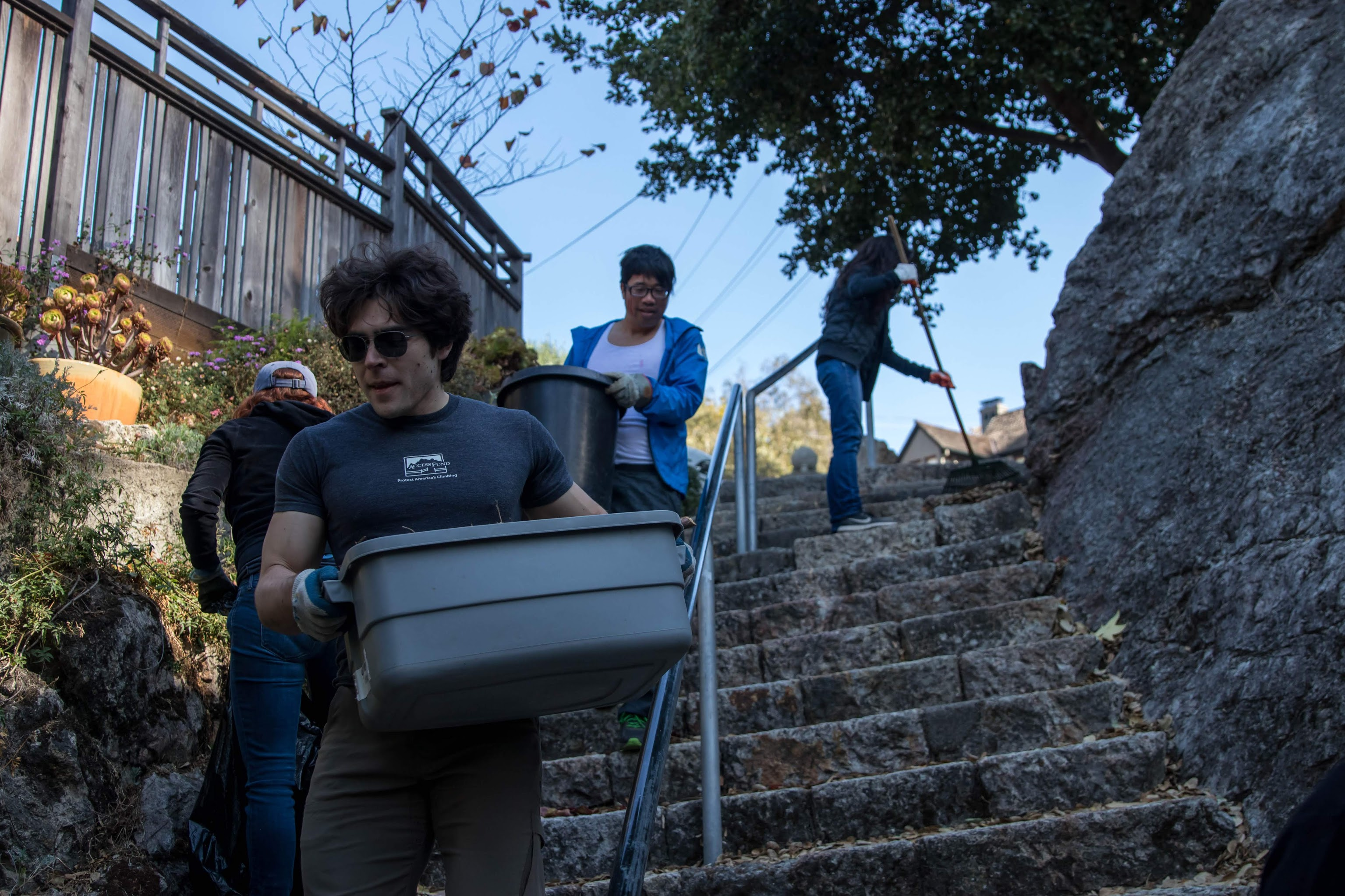 volunteers carry buckets down a stone stairway