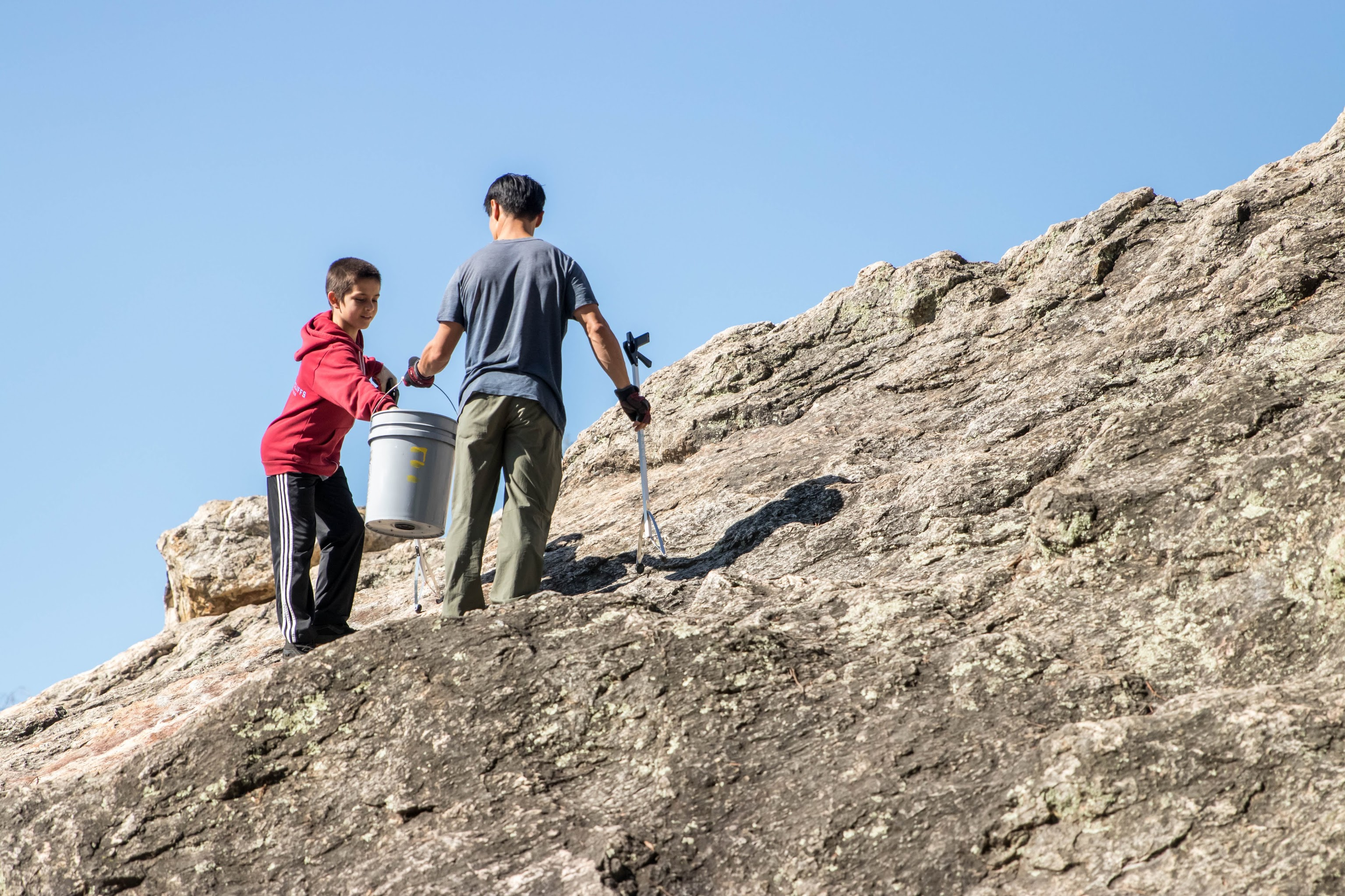 Two volunteers picking up litter on Indian Rock. Both hold grabbing tools. One holds a bucket.