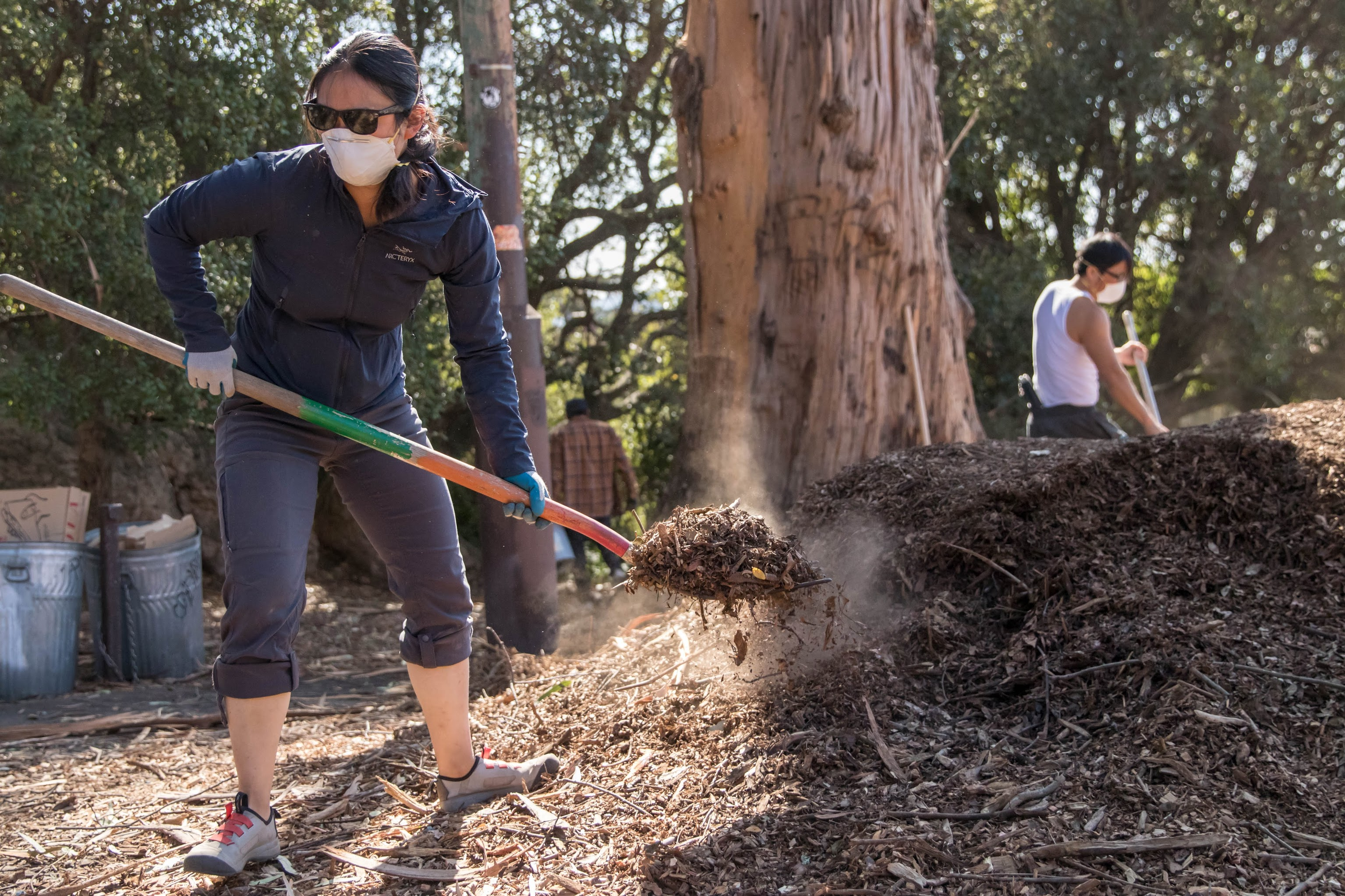 A woman shoveling wood chips while wearing a filtration mask