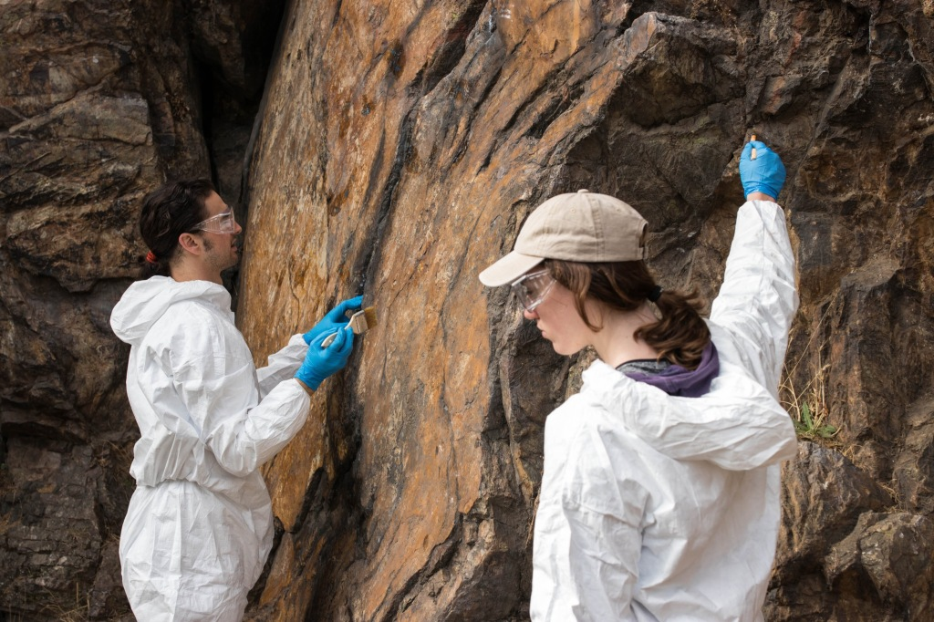 volunteers brushing a graffiti removal paste onto a rock face